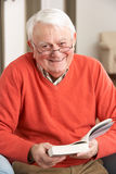 Senior Man Relaxing In Chair At Home Reading Book. Smiling at camera Stock Photos