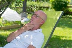 Senior man relaxing in the deckchair in his garden Royalty Free Stock Photos