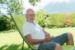 Senior man relaxing in the deckchair in his garden Stock Photography