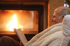 Senior man relaxing by fireplace Stock Photo