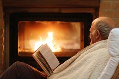Senior man relaxing by fireplace Royalty Free Stock Photos