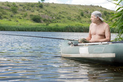 Senior man relaxing fishing from a dinghy Royalty Free Stock Photos