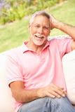 Senior Man Relaxing In Garden Stock Photography