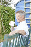 Senior Man Relaxing In Garden With Cup Of Coffee Royalty Free Stock Images