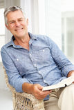 Senior man relaxing at home. With a book smiling to camera Royalty Free Stock Photos