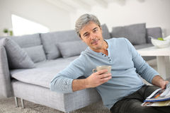 Senior man relaxing at home and drinking coffee Stock Photos