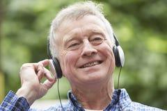 Senior Man Relaxing Listening To Music On Headphones In Garden Stock Images