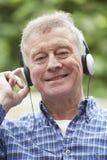 Senior Man Relaxing Listening To Music On Headphones Royalty Free Stock Photo