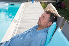 Senior man relaxing outside by swimming pool stock photo