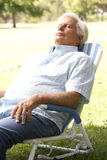 Senior Man Relaxing In Park. On Chair Royalty Free Stock Photography
