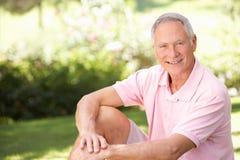 Senior man relaxing in a park Stock Photos