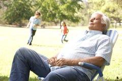 Senior Man Relaxing In Park With Grandchildren. In Background Running stock photo