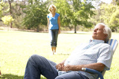 Senior Man Relaxing In Park With Wife. In Background Walking Towards Camera Royalty Free Stock Photo