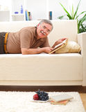 Senior man relaxing and reading. Happy senior man relaxing and reading books on sofa Royalty Free Stock Photo