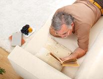 Senior man relaxing and reading. Books on sofa Stock Images