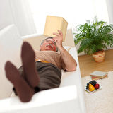 Senior man relaxing and reading. Books on sofa Stock Image