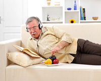 Senior man relaxing and reading Royalty Free Stock Images