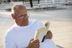 Senior Man Relaxing & Reading. A retired senior spends his golden years reading and relaxing by the pool Stock Photography