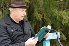 Senior man relaxing reading his book outdoors. Senior gentleman relaxing reading his book outdoors sitting on a garden bench against greenery with a contented Stock Photography