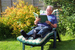 Senior man relaxing and reading on a sun lounger. Royalty Free Stock Images