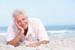Senior Man Relaxing On Sandy Beach Royalty Free Stock Image