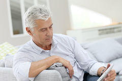 Senior man relaxing on sofa holding tablet Royalty Free Stock Photos