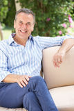 Senior Man Relaxing On Sofa At Home Royalty Free Stock Images