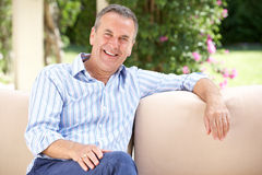 Senior Man Relaxing On Sofa At Home Royalty Free Stock Photo
