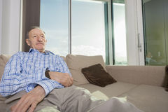 Senior man relaxing on sofa at home Stock Photography