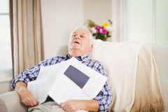 Senior man relaxing on sofa with newspaper Stock Images