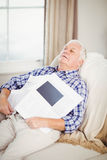 Senior man relaxing on sofa with newspaper Royalty Free Stock Photo