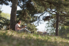 Senior man relaxing under a tree and reading a book in a park in the springtime, Beijing Royalty Free Stock Photography