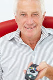 Senior man with remote control Royalty Free Stock Images