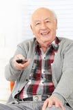 Senior man with remote control. Senior citizen man with remote control watching TV at home Stock Images