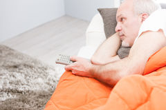Senior man with a remote control on a sofa Royalty Free Stock Photo