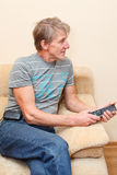 Senior man with remote control and tv-set Royalty Free Stock Image