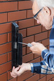 Senior man repairing gate lock Stock Images