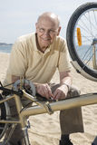 Senior man repairing his bike Royalty Free Stock Image