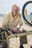 Senior man repairing his bike Royalty Free Stock Image