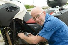 Senior man repairing motorbike outdoor Royalty Free Stock Images