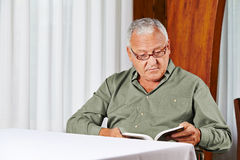 Senior man in rest home reading Royalty Free Stock Image
