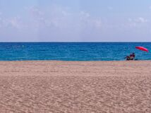 Senior man resting alone on a beautiful white-sand beach somewhere in Spain, turquoise sea on a summer sun