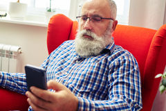 Senior man resting on the chair with smartphone at home Royalty Free Stock Photography