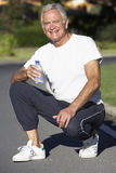 Senior Man Resting And Drinking Water After Exercise Stock Images