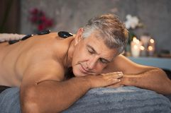 Senior man resting with hot stone massage. Mature man relaxing on bed during hot stone massage. Portrait of senior man with closed eyes resting during lastone royalty free stock photo
