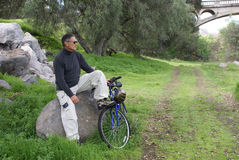Senior Man Resting After Riding Bike. Senior man sitting on a rock after riding his bike or bicycle royalty free stock images