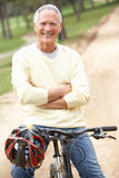 Senior man riding bicycle in park. Smiling Royalty Free Stock Photography