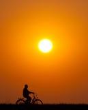 Senior man riding bicycle at sunset. Silhouette of senior man riding bicycle on sunny summer day Royalty Free Stock Photo