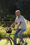 Senior Man Riding Bicycle. Three Quarter View of Senior Man Riding Bicycle Outdoors Stock Photo