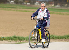 Senior man riding a bike. Active senior man riding a bicycle on countryside stock image
